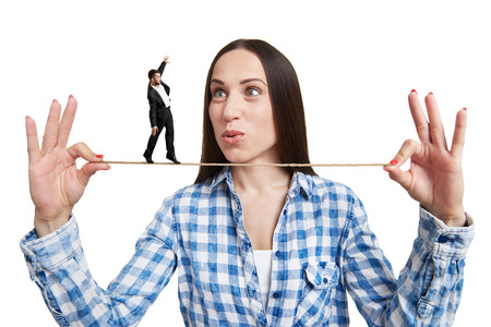 henpecked: amazed woman looking at small man on the rope. isolated on white background