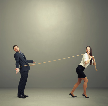 perplexity: laughing woman lugging man in perplexity. photo on dark background Stock Photo