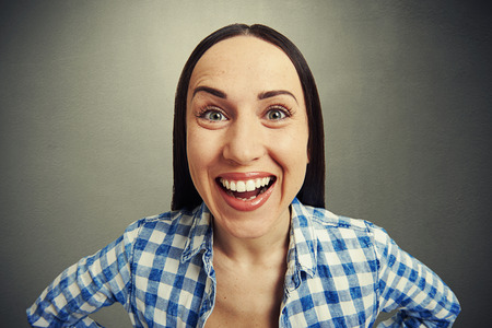 merriment: emotional portrait of laughing woman over grey background