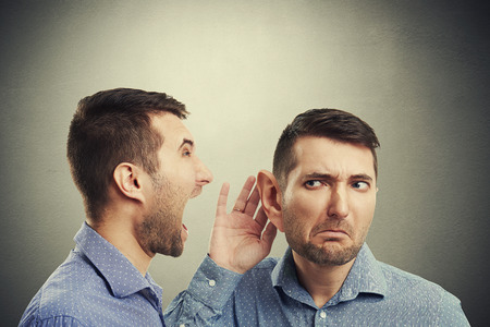 young businessman listening angry screaming man over dark background photo