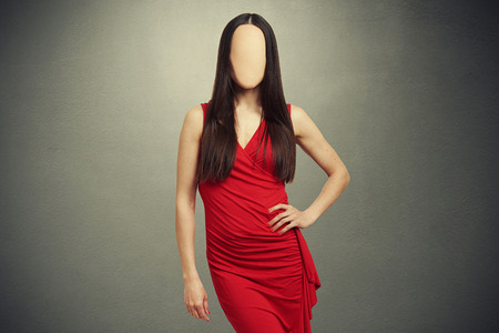 attractive young woman in red dress with empty clear face posing over dark background