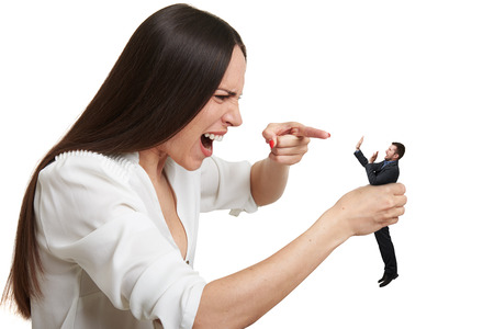 henpecked: emotional yelling woman pointing at small scared man over white background