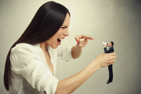 squabble: displeased woman holding small man in hand and they shouting at each other. photo on dark background Stock Photo