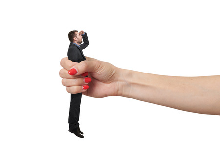 henpecked: amazed man clamped in big female fist and looking up with misunderstanding. isolated on white background Stock Photo