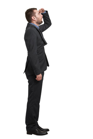 surprised man: amazed businessman in black suit holding his hand on forehead and looking up into the distance. isolated on white background Stock Photo