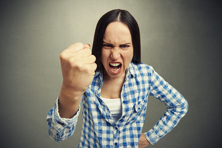 squabble: emotional woman yelling and waving her fist at camera. photo on dark background
