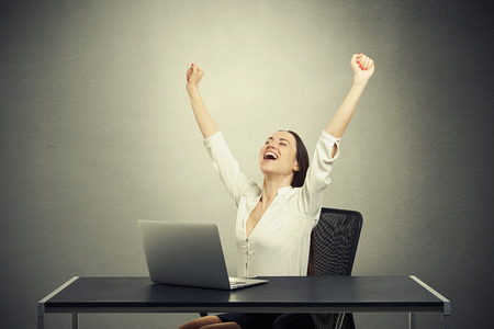 excited happy woman with raised arms sitting at the table against dark background photo
