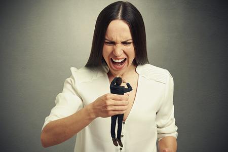 novio: Mujer emocional sosteniendo en peque�o hombre asustado pu�o y grit�ndole. foto en fondo oscuro