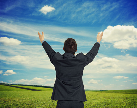 back up: back view of man with hands up against spring nature background