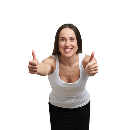 merriment: smiley young woman showing thumbs up and stretching forward. isolated on white background Stock Photo