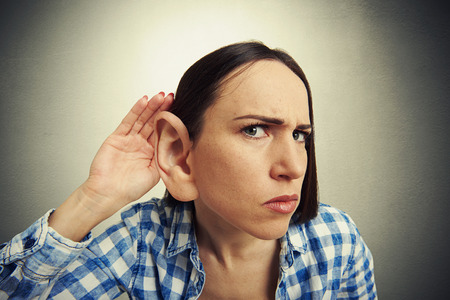 big ear: comic picture of serious woman with one big ear listening attentively and looking at camera. photo on dark background