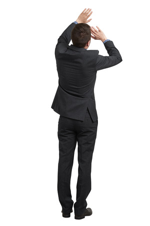 startled: back view of startled businessman in black suit covering himself with his hands. isolated on white background