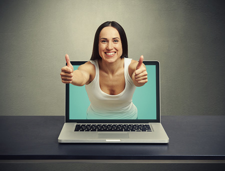 smiley woman stretching out of laptop and showing thumbs up against dark background photo