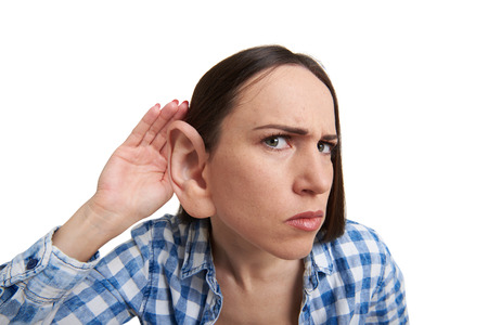 funny picture of serious woman with one big ear listening attentively and looking at camera. isolated on white background