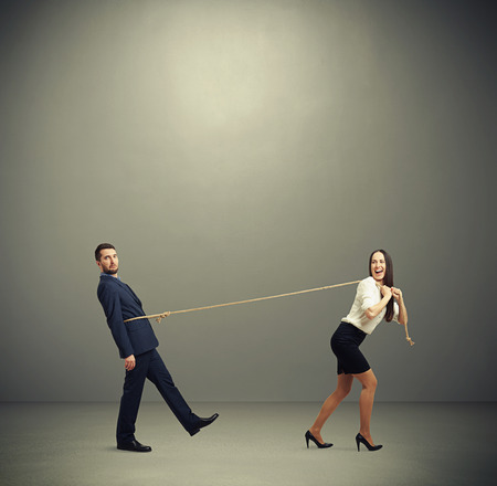 henpecked: concept photo of henpecked husband. happy laughing woman pulling man on the rope and looking at him. photo in empty grey room Stock Photo