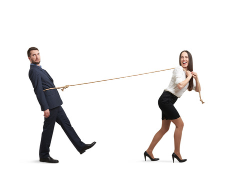 dependent: laughing woman pulling man on the rope and looking at him. man following the woman and looking at camera with perplexity. isolated on white background Stock Photo