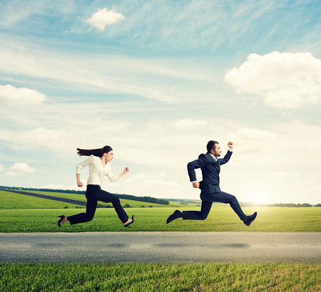 man and woman in formal wear running fast on the road at outdoor against the background of beautiful scenery Stock Photo