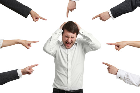 many hands: many fingers pointing at screaming stressed businessman. isolated on white background