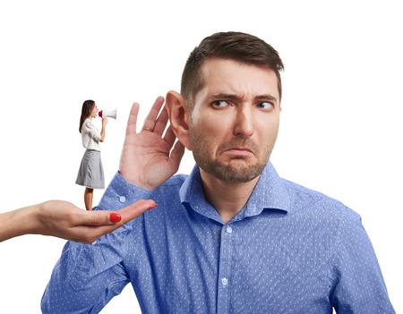 big ear: surrealism photo of hand holding small woman with megaphone that yelling at the man with big ear. isolated on white background