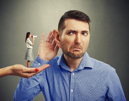 Piccola donna in piedi sul grande mano femminile e grida con il megafono a uomo con grande orecchio su sfondo grigio Archivio Fotografico - 38921505