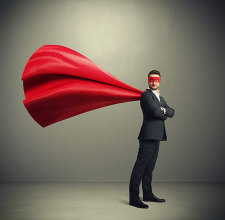 serious businessman dressed as a superhero in red mask and cloak over dark grey background Foto de archivo