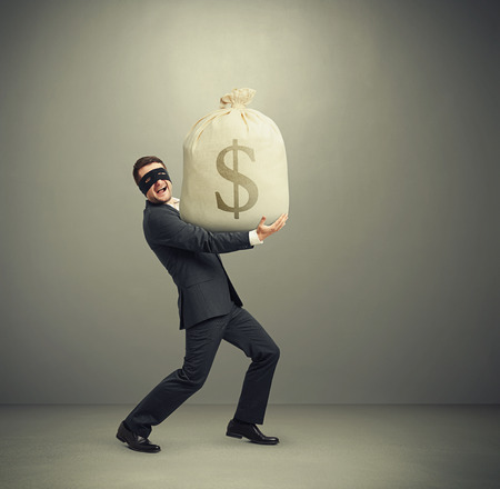 delinquency: laughing man in formal wear and black mask on the eyes holding big bag with money and looking at camera against grey background