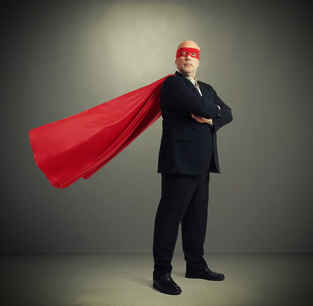 senior businessman dressed as a superhero in red mask and cloak over dark grey background