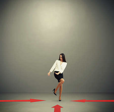 indicate: red arrows indicate at frightened woman in formal wear over dark grey background with empty copyspace overhead