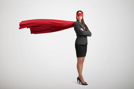 heroes: serious businesswoman dressed as a superhero in red mask and cloak over light grey background