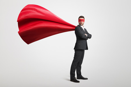 serious businessman dressed as a superhero in red mask and cloak over light grey background