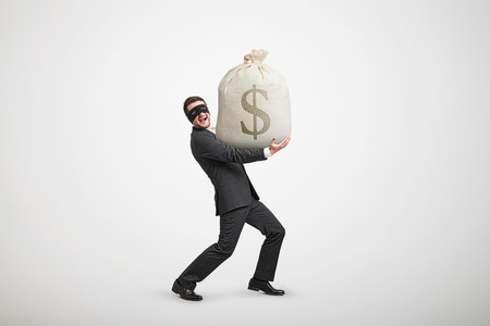 illegality: laughing man in formal wear and black mask on the eyes holding big bag with money and looking at camera against light grey background