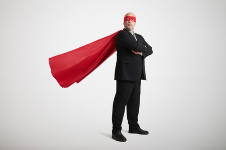 senior businessman dressed as a superhero in red mask and cloak over light grey background