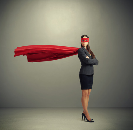 super human: serious businesswoman dressed as a superhero in red mask and cloak over dark grey background