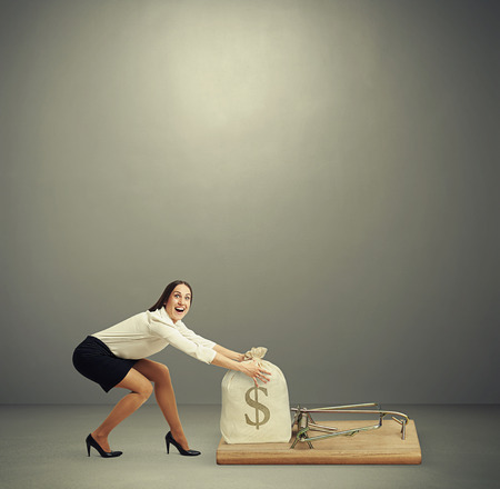 excited woman in formal wear reaching her arms to take bag with money in big mousetrap over dark grey background with empty copyspace overhead