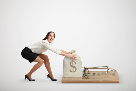 avidity: excited woman in formal wear reaching her arms to take bag with money in big mousetrap over light grey background Stock Photo