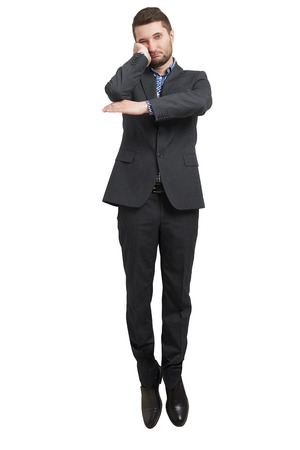 lazybones: tired businessman hanging in the air and looking at camera. isolated on white background
