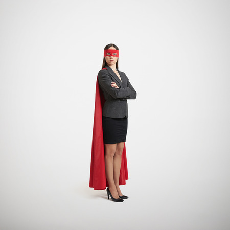 serious businesswoman dressed as a superhero in red mask and cloak over light grey background
