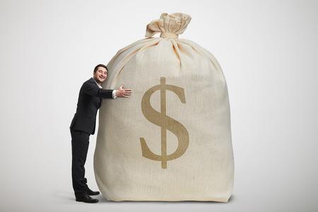 prosperidad: hombre feliz abrazando gran bolsa con dinero sobre fondo gris claro