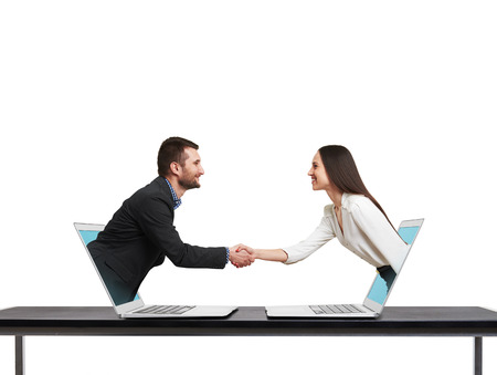 smiley businessman and businesswoman come out from laptop, shaking hands and looking at each other over white background
