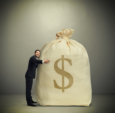 happy man embracing big bag with money over dark grey background