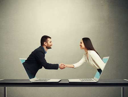 smiley businessman and businesswoman come out from laptop, shaking hands and looking at each other over dark grey background