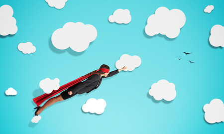 superwoman in red mask and cloak flying through paper clouds over blue background Stock Photo