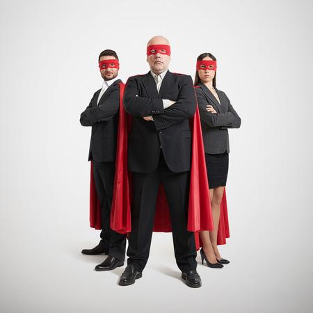 full length portret van drie superhelden in formele slijtage en rode masker met mantel over lichtgrijze achtergrond