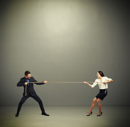 business rival: woman and man in formal wear pulling the rope over dark grey background