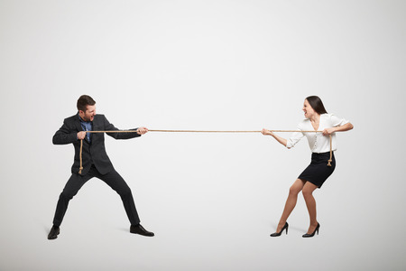 conflicts: woman and man in formal wear pulling the rope over light grey background