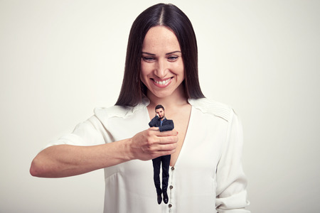 wearied: smiley woman holding small wearied man in her fist over light grey background