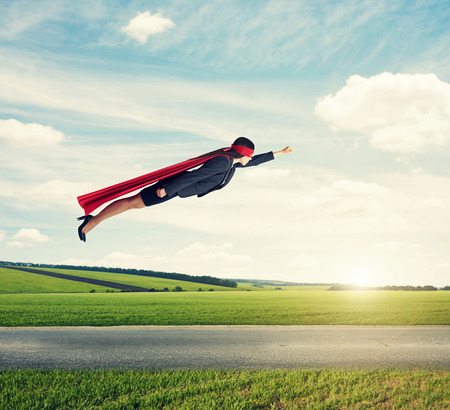serious businesswoman dressed as a superhero in red mask and cloak flying at outdoor over beautiful landscape background
