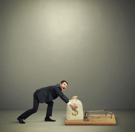 大きなネズミ捕りのお金でバッグを引き継ぐ空 copyspace オーバーヘッドと暗い灰色の背景に彼の手を到達正式な摩耗で驚かれる男