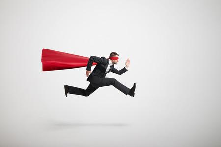 ernstige zakenman draagt als superheld zeer snel loopt over lichtgrijze achtergrond Stockfoto