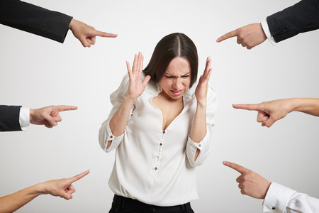 reprimand: many fingers pointing at stressed businesswoman over light grey background Stock Photo